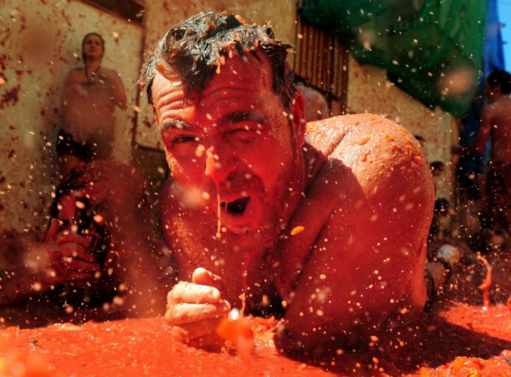 A reveller swims in tomato pulp during La Tomatina festival, the world's biggest tomato fight on August 25, 2010 in Bunol, Spain. More than 45000 people from all over the world descended on the small Valencian town to participate in this year's La Tomatina festival, with the local town hall estimating that over 100 tons of rotten and over-ripe tomatoes were thrown. (Photo by Jasper Juinen/Getty Images)