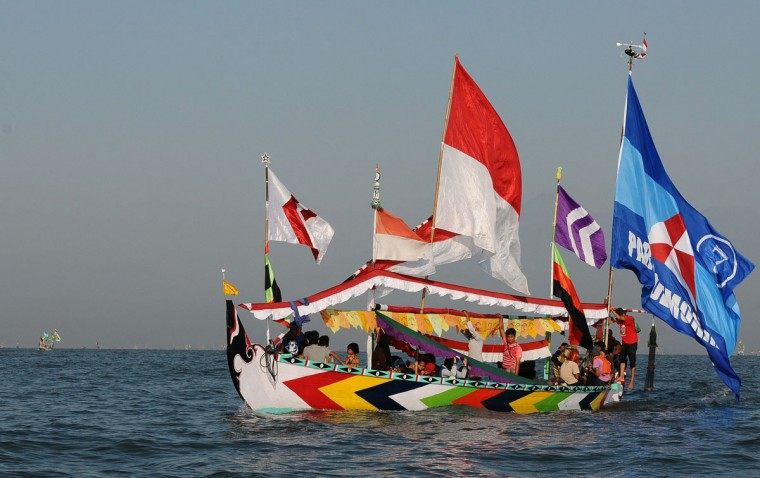 Indonesian fishermen and his family sail for the Petik Laut ceremony in specially decorated boats on August 4, 2014 in Pasuruan, Java, Indonesia. Indonesian Muslims working as fishermen have a tradition called Petik Laut, a ceremony in which they make offerings to Gods of the sea and give thanks for a plentiful harvest as part of Eid celebrations. They decorated the boat, make offerings, and sail to the sea follow the Petik Laut ceremony. (Robertus Pudyanto/Getty Images)