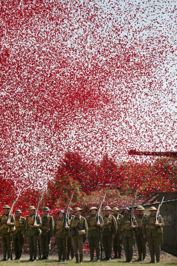 Members of the Great War Society living history group dressed as 4th Battalion the Middlesex Regiment stand under a shower of a million poppy flowers representing the dead during a World War One centenary ceremony at the Tank Museum, Bovington on August 4, 2014 in England. Monday August 4, 2014 marks the 100th anniversary of Great Britain's declaration of war on Germany. In 1914 British Prime Minister Herbert Asquith announced at 11 pm that Britain was to enter the war after Germany had violated Belgium neutrality. The First World War or the Great War lasted until 11 November 1918 and is recognized as one of the deadliest historical conflicts with millions of causalities. A series of events commemorating the 100th anniversary are taking place throughout the day. (Peter Macdiarmid/Getty Images)