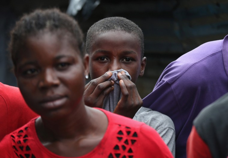 Local residents watch as others dress a sick Saah Exco, 10, after bathing him in a back alley of the West Point slum on August 19, 2014 in Monrovia, Liberia. According to community organizer John Saah Mbayoh, Saah's mother died of suspected but untested Ebola in West Point before he was brought to the isolation center the evening of August 13. He came with his brother, Tamba, 6, aunt Ma Hawa, and cousins. His brother died on August 15 at the center. Saah fled the center the August 15 with several other patients before it was overrun on August 16 by a mob. Once out in the neighborhood, he was not sheltered, as he had suspected Ebola - so he has been sleeping outside. Residents reportedly began giving him medication, a drip and oral rehydration liquids today. The whereabouts and condition of his aunt and cousins, who left the facility when it was overran by the crowd, is still unknown at this time. The Ebola virus has killed more than 1,000 people in four African nations, more in Liberia than any other country. (Photo by John Moore/Getty Images)