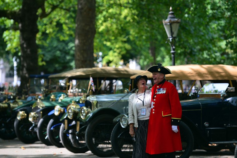 A Chelsea Pensioner, British war veterans from the Chelsea Royal Hospital, shares a joke with a companion as they walk amongst World War 1 era cars in central London on August 4, 2014 as part of a Great War Centenary Parade: a procession of more than 40 Edwardian cars to commemorate Britain's entry into World War 1. Britain ran a series of events as part of the commemoration of the 100th anniversary of the outbreak of World War I, a small Balkans conflict that went global with the German invasion of neutral Belgium in August 1914 which Britain entered on August 4, 2014. (Carl Court/AFP/Getty Images)