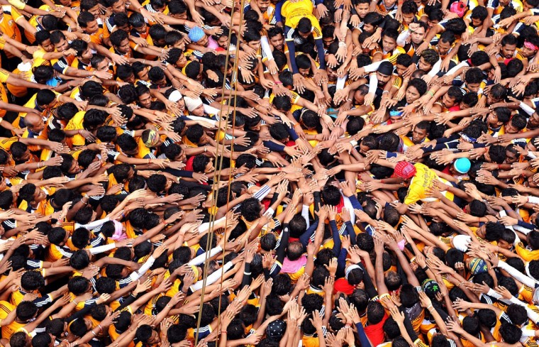 Indian Hindu devotees gesture before attempting to form a human pyramid in a bid to reach and break a dahi-handi (curd-pot) suspended in air during celebrations for the Janmashtami festival, which marks the birth of Hindu god Lord Krishna, in Mumbai on August 18, 2014. (INDRANIL MUKHERJEE/AFP/Getty Images)