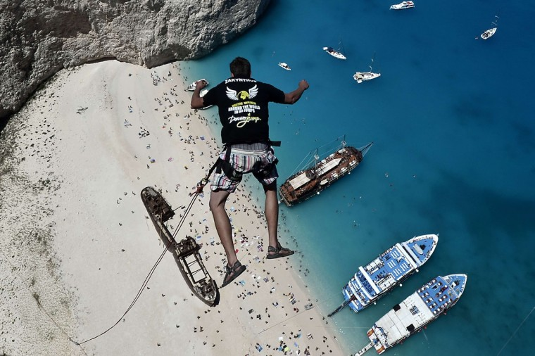 Lukas Michul, a member of the 'dream walker' group jumps from atop the rugged rocks overlooking the azure waters of Navagio beach, one of the Greece's most renowned leisure spots on the popular tourist island of Zakynthos on June 23, 2014. This is rope jumping -- part diving, part rock climbing, with a touch of engineering. The aim of the project is to dream jump in 80 places with most ravishing nature and architecture all over the world .They plan to stage their next leaps at a cave complex in Croatia, a French viaduct, skyscrapers in Las Vegas and Johannesburg, and the Grand Canyon. (AFP PHOTO/Getty Images/Louisa Gouliamaki)