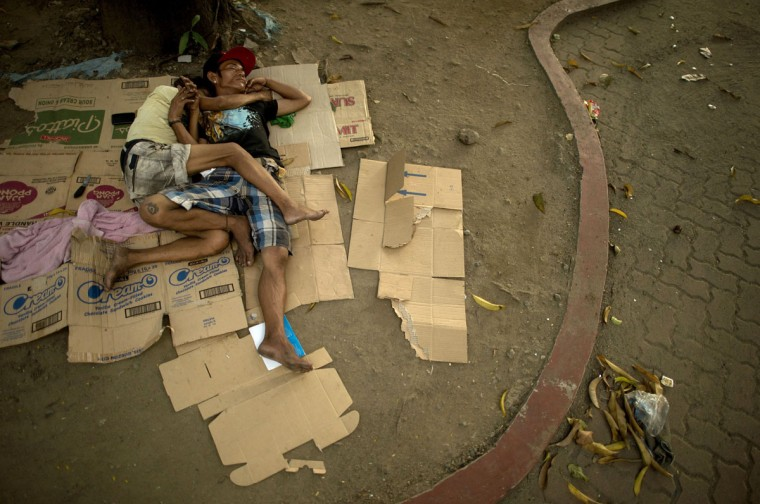 Homeless people sleep on the ground at a park in Manila on August 24, 2014. (NOEL CELIS/AFP/Getty Images)