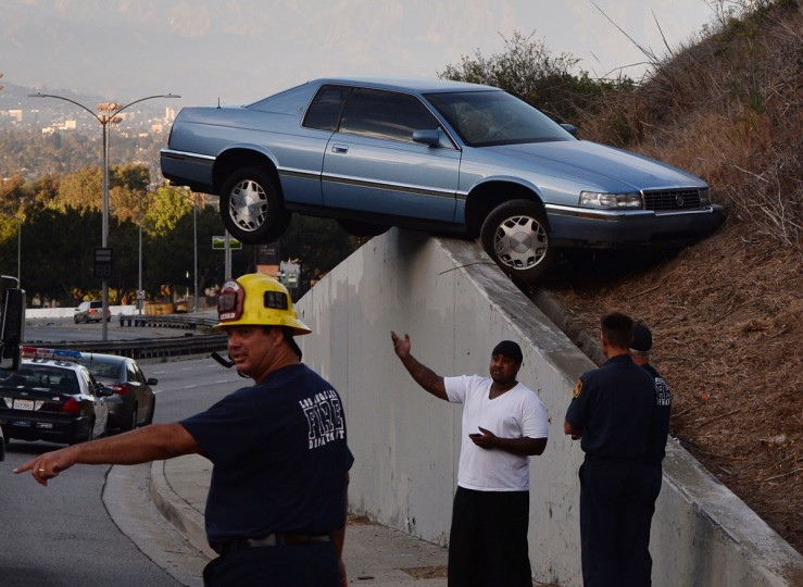 A car sits atop an embankment after losing control and skidding up the concrete retaining wall on South La Brea Ave in Baldwin Hills, Los Angeles on August 24, 2014. The driver and his passenger escaped injury. (MARK RALSTON/AFP/Getty Images)