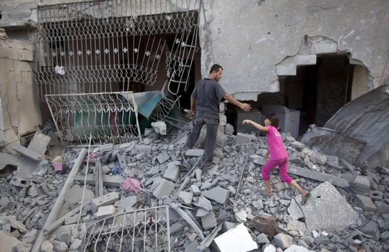 Palestinians walk through the rubble of a house after it was hit in an Israeli air strike in Gaza City on August 25, 2014. (MAHMUD HAMS/AFP/Getty Images)