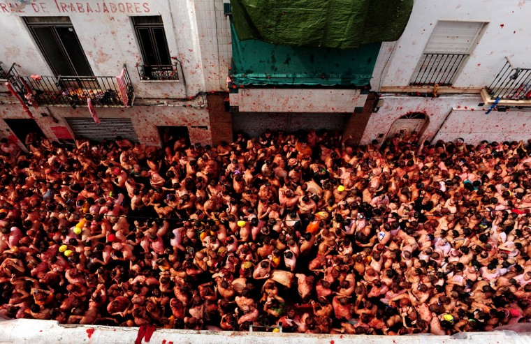 Revellers pelt each other with tomatoes during the world's biggest tomato fight at La Tomatina festival on August 26, 2009 in Bunol, Spain. More than 45000 people from all over the world descended on the small Valencian town to participate in this year's La Tomatina festival, with the local town hall estimating that over 100 tons of rotten and over-ripe tomatoes were thrown. (Photo by Jasper Juinen/Getty Images)
