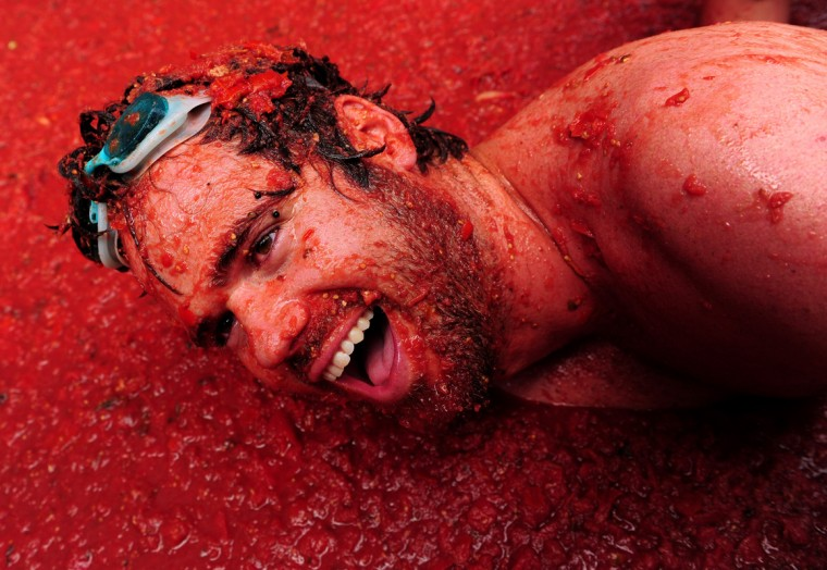 A reveller lays in tomato pulp during the world's biggest tomato fight at La Tomatina festival on August 26, 2009 in Bunol, Spain. More than 45000 people from all over the world descended on the small Valencian town to participate in this year's La Tomatina festival, with the local town hall estimating that over 100 tons of rotten and over-ripe tomatoes were thrown. (Photo by Jasper Juinen/Getty Images)