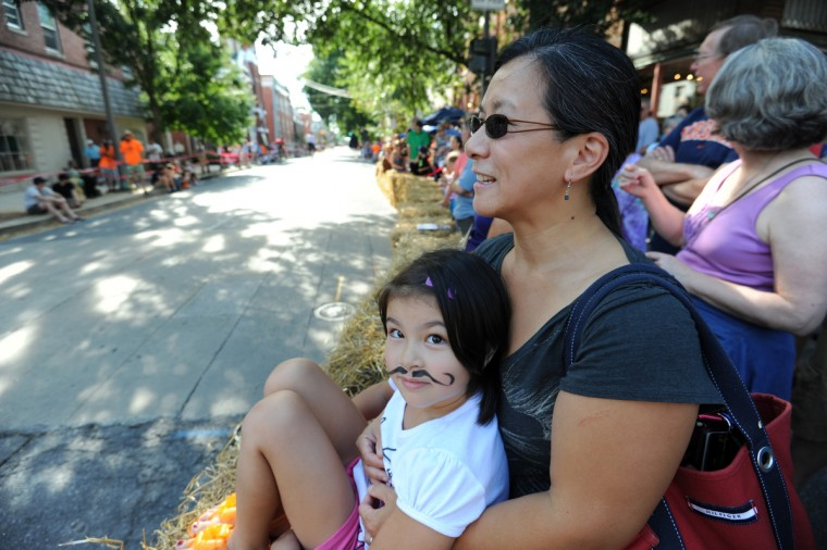 Susan Au of Frederick, and her daughter, Jaedyn Fitzpatrick, 7, wait for riders doing laps in the 2014 Frederick Clustered Spires High Wheel Race. (Kim Hairston/Baltimore Sun)