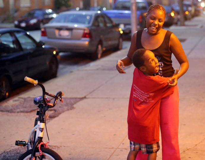 Isaiah Turner, 8, hugs Amyra Carr, 10, as she begins to sing outside of their home in West Baltimore before the 9pm curfew for youth in Baltimore City. (Al Drago/Baltimore Sun)