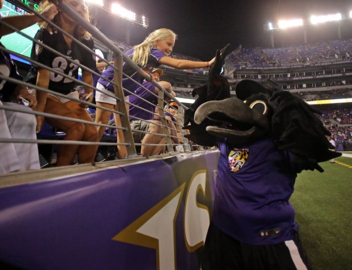A young fan high fives the Ravens Mascot Poe in the second half as the Baltimore Ravens take on the San Francisco 49ers at M&T Bank Stadium in Baltimore, MD on Thursday, August 7, 2014. (Al Drago/Baltimore Sun)