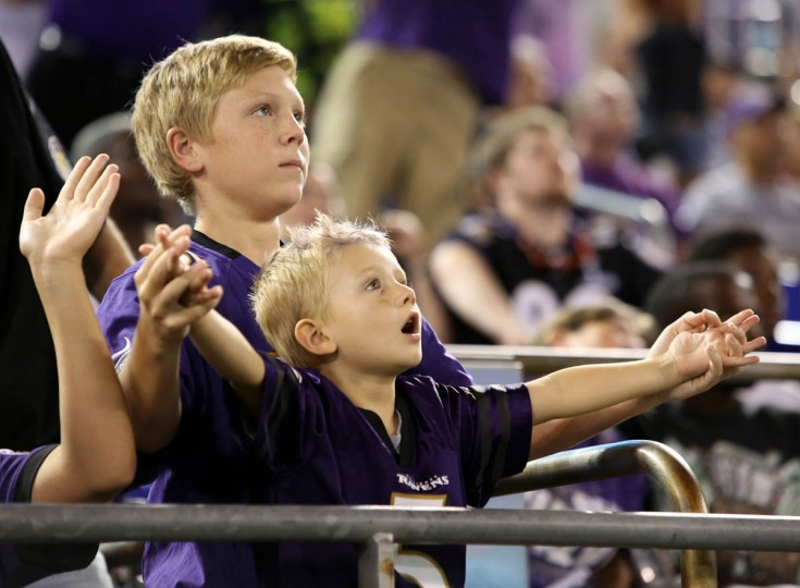 Zach Szczybor, 14, holds hands with Drew Hacke, 5, of Kingsville, as the Ravens go for an extra three points as the Baltimore Ravens take on the San Francisco 49ers at M&T Bank Stadium in Baltimore, MD on Thursday, August 7, 2014. (Al Drago/Baltimore Sun)