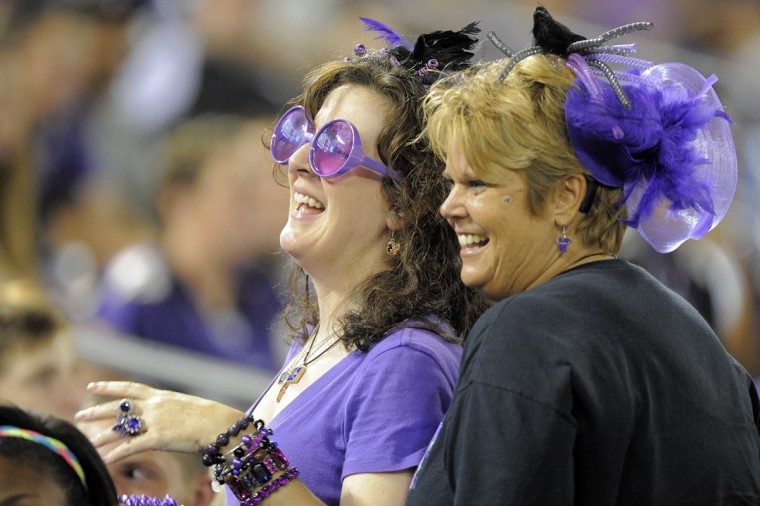 Fans decked out in purple regalia smile for a photo in the second half as the Baltimore Ravens take on the San Francisco 49ers at M&T Bank Stadium in Baltimore, MD on Thursday, August 7, 2014. (Al Drago/Baltimore Sun)