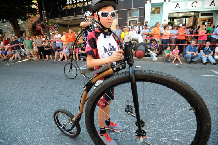 Haken Rhoten, 9, waits to ride in the 2014 Frederick Clustered Spires High Wheel Race. His father, Chris Rhoten, built the frame of the penny farthing bicycle from a scythe snath. (Kim Hairston/Baltimore Sun)