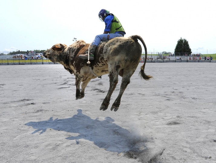 BJ Greene of Middletown H.S. in Frederick hangs on to a bull as he comes out of the chute. (Lloyd Fox/Baltimore Sun)