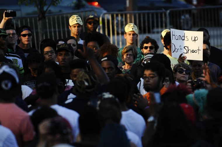"""A protestor's sign reads """"hands up don't shoot"""" in the middle of the crowd at the inner harbor during the solidarity rally and march Thursday evening for Michael Brown of Ferguson, Missouri. (Rachel Woolf/Baltimore Sun)"""