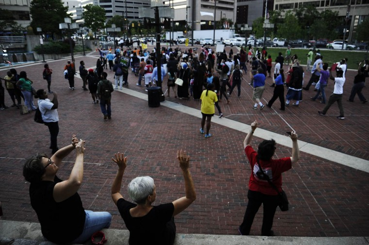 "A crowd gathers in the inner harbor chanting ""hands up don't shoot"" Thursday evening at the solidarity rally and march for Michael Brown of Ferguson, Missouri. (Rachel Woolf/Baltimore Sun)"