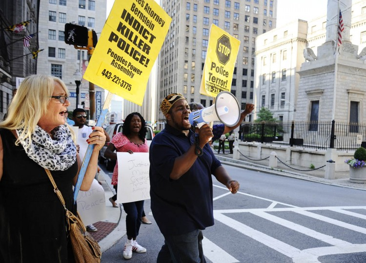 From left, Donna Plamondon and Elder C.D. Witherspoon lead the march to the Baltimore Police Department Thursday evening outside of the Clarence Mitchell Jr. Courthouse during the solidarity rally and march Thursday evening for Michael Brown of Ferguson, Missouri. (Rachel Woolf/Baltimore Sun)