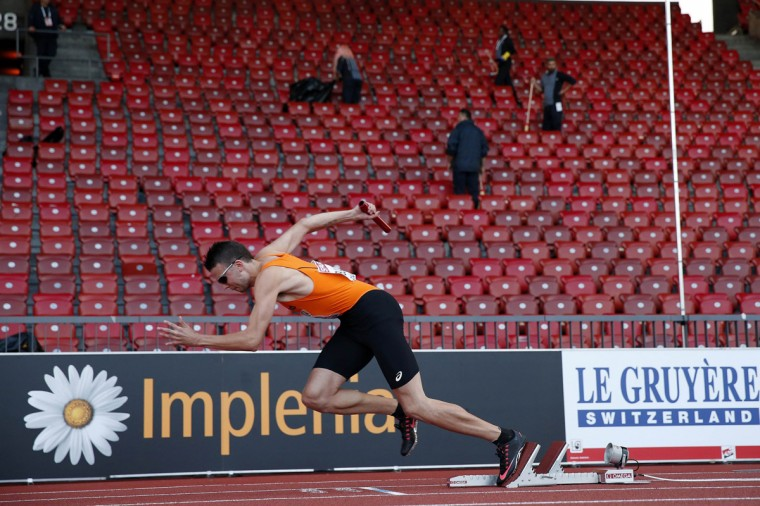 Bjorn Blauwhof of the Netherlands leaves his blocks at the start of the re-running of their 4 x 400 metres relay heat as cleaners work in an empty stadium during the European Athletics Championships in Zurich, August 16, 2014. The Netherlands quartet had to run their heat again at the end of the session after successfully appealing an earlier disqualification. REUTERS/Phil Noble