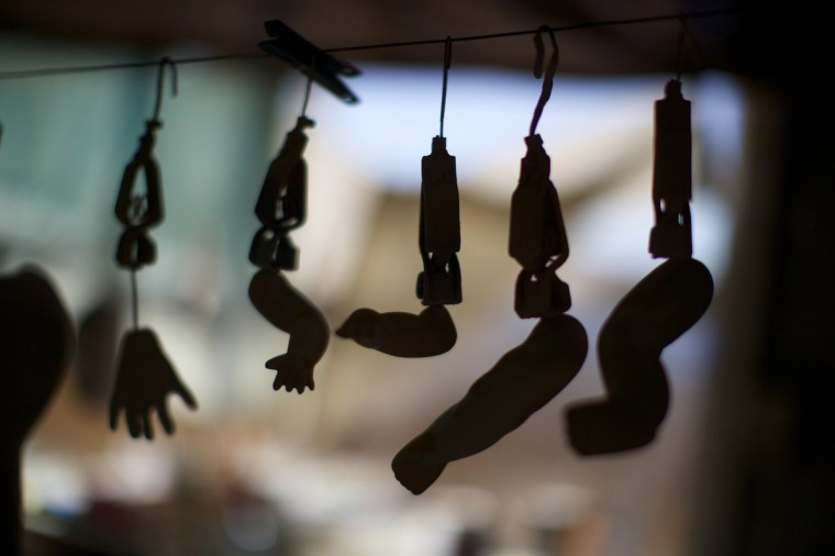 The arms, legs and hands of composition dolls, made from compressed wood chip, are pictured hanging on a line as the paint dries in a workshop of Sydney's Doll Hospital. (Jason Reed/Reuters)