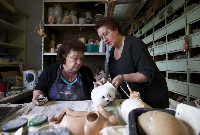 Doll restorers Gail Grainger (L) and Kerry Stuart inspect the head of a composition doll, made from compressed wood chip, in the workshop of Sydney's Doll Hospital. (Jason Reed/Reuters)