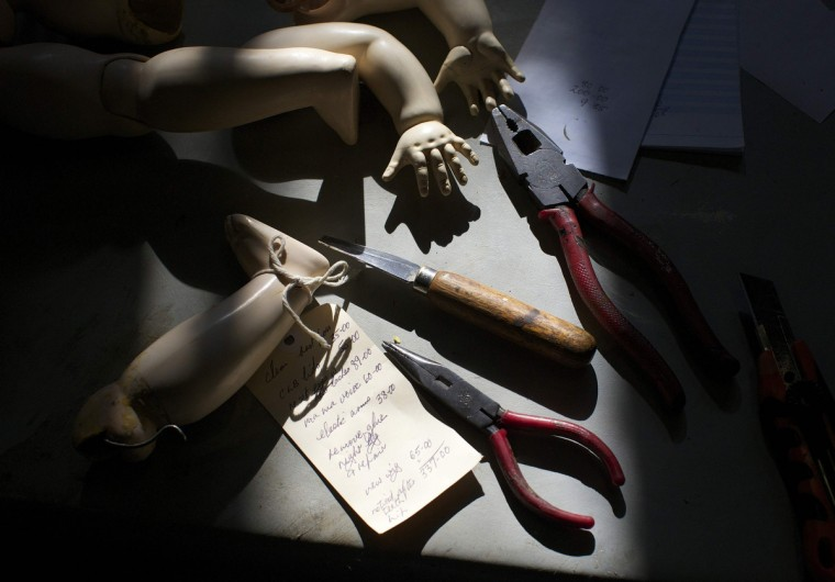Doll limbs and hand tools are pictured in the afternoon sun on the work bench of Geoff Chapman, 'Head Surgeon' and owner of Sydney's Doll Hospital. (Jason Reed/Reuters)