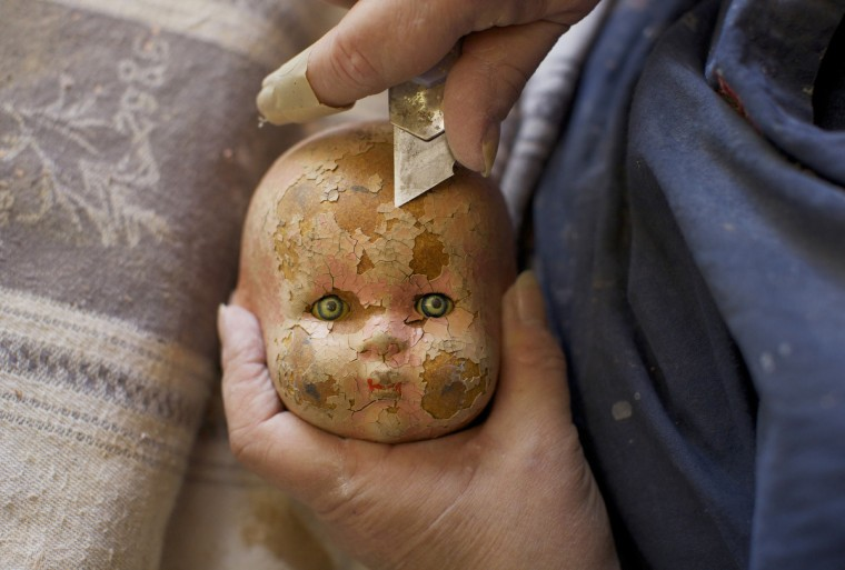 A badly-weathered composition doll, made from compressed wood chip, has its flakey paint cut off before being repaired and repainted by Gail Grainger, a 14-year veteran doll repairer at Sydney's Doll Hospital. (Jason Reed/Reuters)