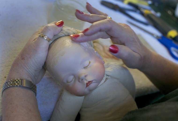Doll restorer Kerry Stuart rubs a filling compound into the cracked head of a plastic doll at Sydney's Doll Hospital. (Jason Reed/Reuters)