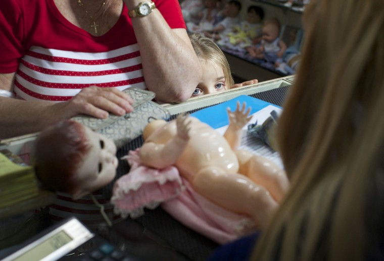 A young customer looks over the counter as a family member brings in a doll for repair at Sydney's Doll Hospital. (Jason Reed/Reuters)
