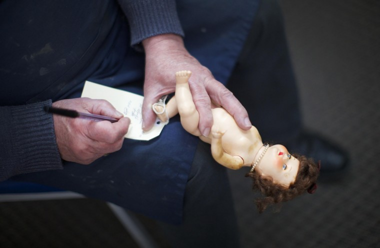 Geoff Chapman, 'Head Surgeon' and third-generation owner of Sydney's Doll Hospital, holds a small doll on one hand as he writes details onto its repair card attached to its foot, at his workshop. (Jason Reed/Reuters)