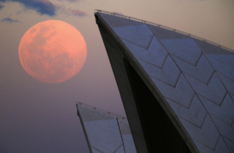 A supermoon rises behind the roof of the Sydney Opera House August 10, 2014. The astronomical event occurs when the moon is closest to Earth in its orbit, making it appear much larger and brighter than usual. (David Gray/Reuters)