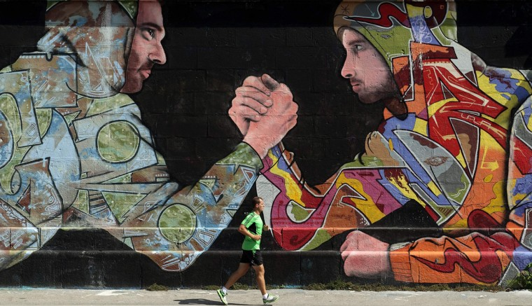 A jogger runs past a mural on a wall on a sunny summer day in Vienna, August 21, 2014. (Heinz-Peter Bader/Reuters)