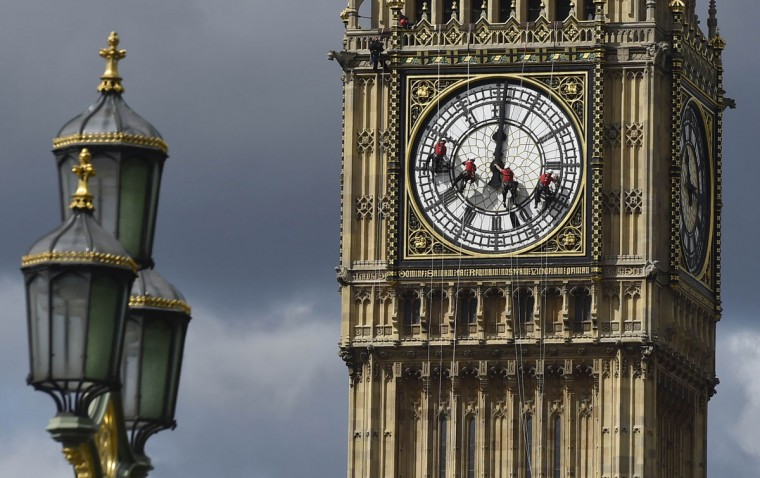 Cleaners abseil down one of the faces of Big Ben, to clean and polish the clock face, above the Houses of Parliament, in central London August 19, 2014. A week has been set aside for the cleaning of what is officially known as the Great Clock, which is set in the Elizabeth Tower. (REUTERS/Toby Melville)