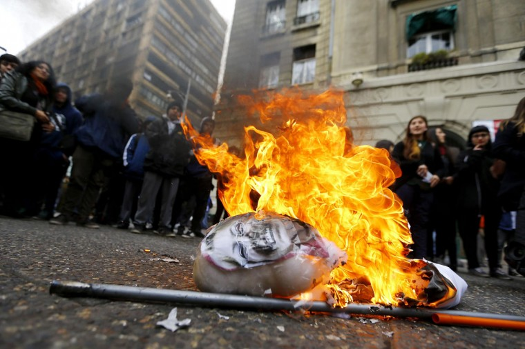 High school students gather around a burning effigy representing Chile's President Michelle Bachelet during a rally in front of Santiago's town hall, August 19, 2014. The rally was held after the Santiago Court of Appeals ruled in favor of prohibiting the occupations of educational institutions by students. (REUTERS/Ivan Alvarado)