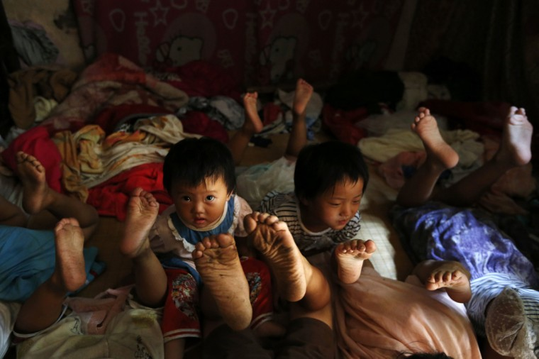 Shiyu, 1, the youngest child of a seven-children family, looks up as she rests on a bed at home with her brothers and sisters, in Jinhua, Zhejiang province, August 7, 2014. Migrant worker Yang Hongnian, 47, his wife Le Huimin, and their seven children share a 20-square-metre makeshift house on the outskirts of Jinhua, and live on around 3000-4000 yuan ($486.8-$649) which Yang earns from working at a construction site. Except for one daughter Le had with her ex-husband, the couple have given birth to six children in 10 years. (William Hong/Reuters)