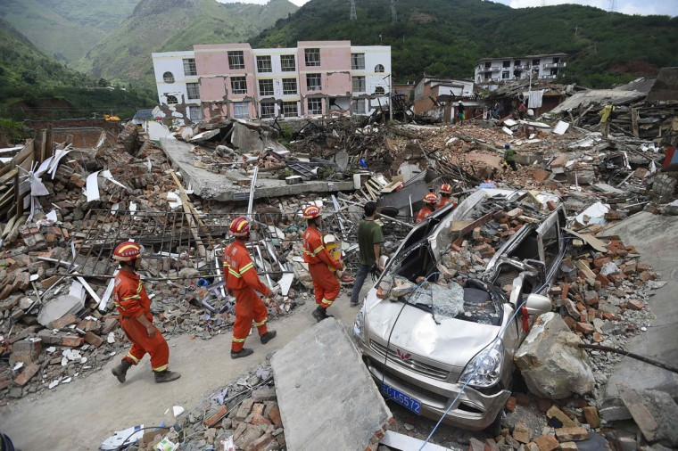 Rescue workers walk past debris of houses at an earthquake zone in Ludian county, Zhaotong, Yunnan province, August 5, 2014. An earthquake in China on the weekend triggered landslides that have blocked rivers and created rapidly growing bodies of water that could unleash more destruction on survivors of the disaster that killed 410 people, state media reported on Thursday. (REUTERS/Stringer)