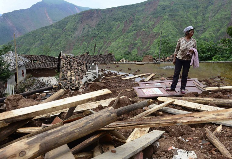 A woman looks around at the debris after her house collapsed due to a magnitude 6.3 earthquake that hit Longtoushan town, Ludian county of Zhaotong, Yunnan province August 4, 2014. The death toll from the earthquake that hit southwestern China on Sunday climbed to 398 people, state media reported on Monday. Picture taken August 4, 2014. (REUTERS/Stringer)