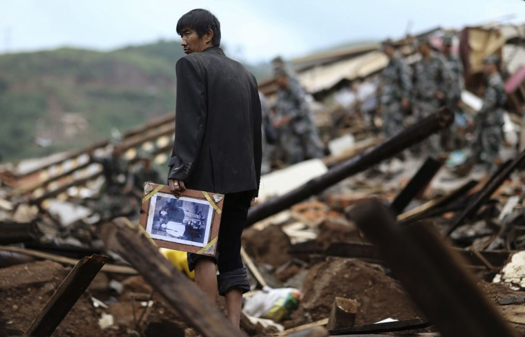 A man holds a picture as he stands among debris of collapsed buildings after an earthquake hit Longtoushan township of Ludian county, Yunnan province August 4, 2014. A magnitude 6.3 earthquake struck southwestern China on Sunday, killing at least 398 people in a remote area of Yunnan province, and causing thousands of buildings, including a school, to collapse. (Wong Campion/Reuters)