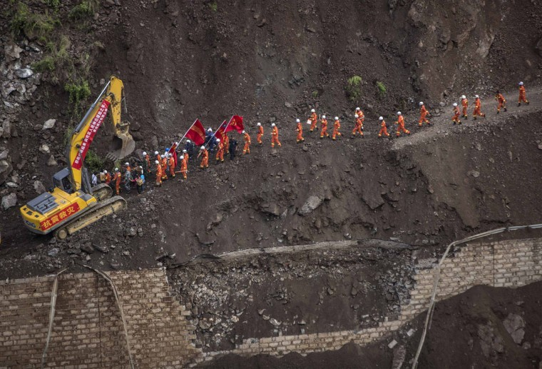 A group of rescue workers walk through a collapsed road at an earthquake hit area in Ludian county, Zhaotong, Yunnan province, August 5, 2014. An earthquake in China on the weekend triggered landslides that have blocked rivers and created rapidly growing bodies of water that could unleash more destruction on survivors of the disaster that killed 410 people, state media reported on Thursday. (REUTERS/Stringer)