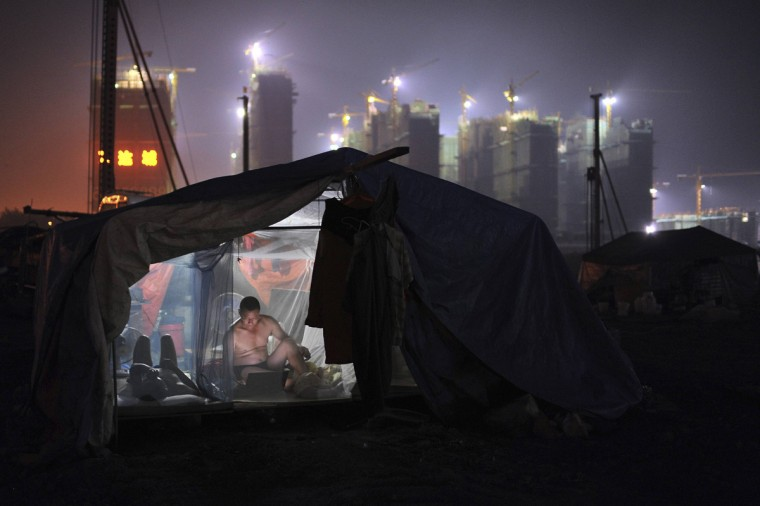 A worker uses a laptop inside his dormitory near a residential construction site in Hefei, Anhui province August 6, 2014. A raft of China data over the coming week will give the first indications of the economy's third-quarter performance, after conflicting signals suggested that more stimulus measures may be needed to ensure a sustained recovery. (Reuters)