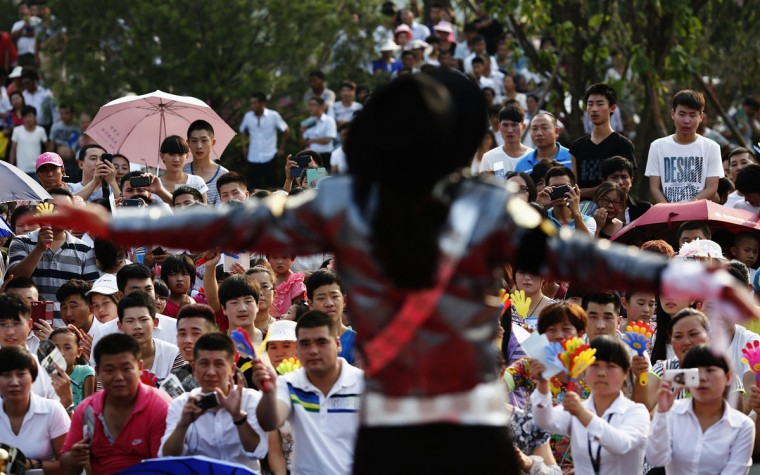 Zhang Guanhui, imitating Michael Jackson, performs during a small music concert in Langfang, Hebei province July 19, 2014. Zhang, born in 1984, quit elementary school and has since held jobs as a factory worker, waiter, and security guard. After watching a Michael Jackson music video four years ago for the first time, Zhang says he became fascinated and now puts on shows on the street and small stages impersonating the King of Pop. (Kim Kyung-Hoon/Reuters)