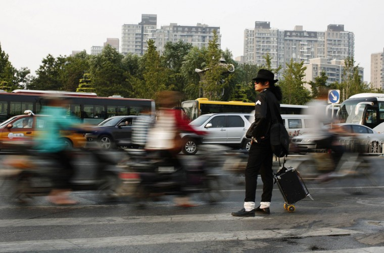 Zhang Guanhui, impersonating Michael Jackson, waits to cross a street as he heads downtown for his street performance in Beijing August 20, 2014. Zhang, born in 1984, quit elementary school and has since held jobs as a factory worker, waiter, and security guard. After watching a Michael Jackson music video four years ago for the first time, Zhang says he became fascinated and now puts on shows on the street and small stages impersonating the King of Pop. Picture taken August 20, 2014. (Kim Kyung-Hoon/Reuters)