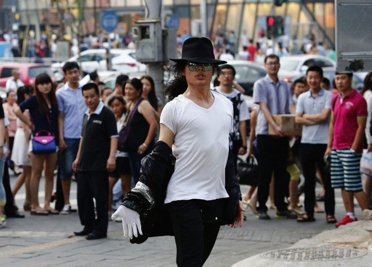 Zhang Guanhui, impersonating Michael Jackson, dances during his street performance in Beijing August 20, 2014. Zhang, born in 1984, quit elementary school and has since held jobs as a factory worker, waiter, and security guard. After watching a Michael Jackson music video four years ago for the first time, Zhang says he became fascinated and now puts on shows on the street and small stages impersonating the King of Pop. Picture taken August 20, 2014. (Kim Kyung-Hoon/Reuters)