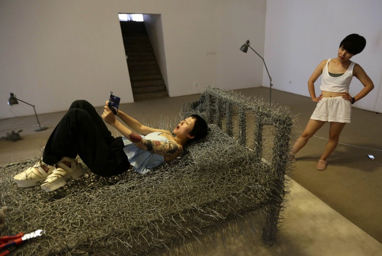 "Chinese artist Zhou Jie (R) looks at her friend who is taking a ""selfie"" on an unfinished iron wire bed, one of Zhou's sculptures, while visiting her at Beijing Art Now Gallery, in Beijing August 11, 2014. Zhou started her art project titled ""36 Days"" on August 9, in which she would live inside an exhibition hall with an unfinished iron wire bed, some iron wire sculptures in the shape of stuffed animal dolls, a certain amount of food and her mobile phone, for 36 days. The entire process is open to visitors and she may also interact with them, according to Zhou. Picture taken August 11, 2014. (Jason Lee/Reuters)"