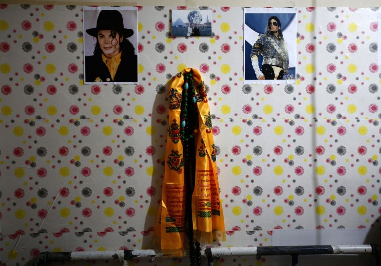 Pictures of Michael Jackson are hung on a wall in a small one-room house Zhang Guanhui, a Michael Jackson impersonator, in Beijing July 22, 2014. Zhang, born in 1984, quit elementary school and has since held jobs as a factory worker, waiter, and security guard. After watching a Michael Jackson music video four years ago for the first time, Zhang says he became fascinated and now puts on shows on the street and small stages impersonating the King of Pop. (Kim Kyung-Hoon/Reuters)