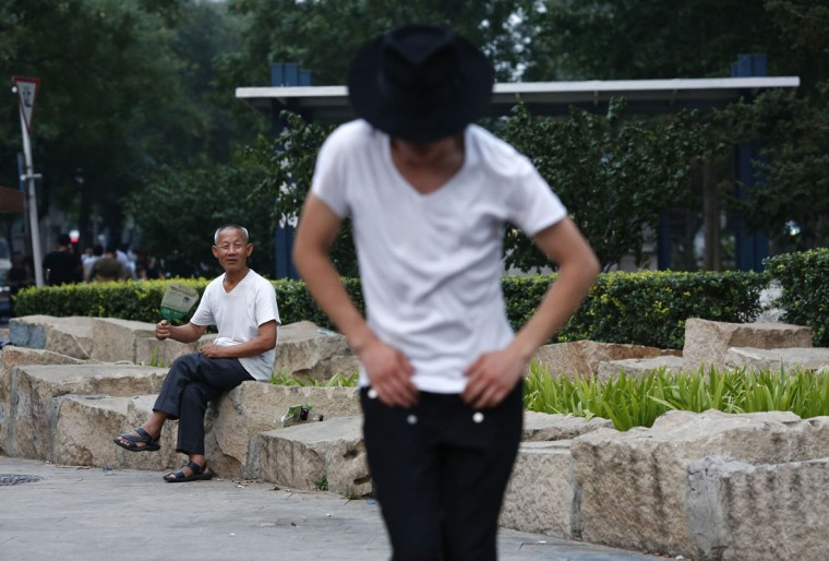 A man watches a street performance by Zhang Guanhui, impersonating Michael Jackson, in Beijing August 20, 2014. Zhang, born in 1984, quit elementary school and has since held jobs as a factory worker, waiter, and security guard. After watching a Michael Jackson music video four years ago for the first time, Zhang says he became fascinated and now puts on shows on the street and small stages impersonating the King of Pop. Picture taken August 20, 2014. (Kim Kyung-Hoon/Reuters)