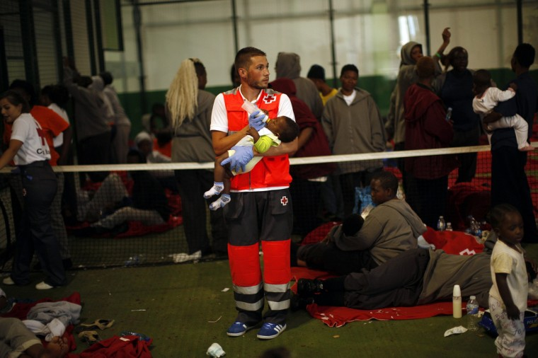 A member of Spanish Red Cross feeds an African immigrant's baby next to other African migrants as they rest inside a paddle court inside a sports centre after arriving on a rescue ship at the southern Spanish port of Tarifa, near Cadiz, southern Spain. Spanish emergency services picked up some 920 immigrants travelling in about 81 rafts across the Strait of Gibraltar on Tuesday, a spokesman for the Spanish Red Cross said. (Jon Nazca/Reuters)