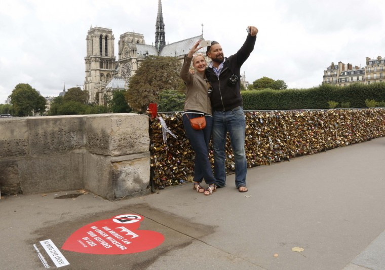 """Newlyweds Regina and Vadim Medvedev from Riga in Latvia, take selfies on the Pont de l'Archeveche bridge, which is covered with thousands of padlocks, called love locks, near the Notre Dame Cathedral in Paris . On the pavement is a large red heart with the message """"Our bridges can no longer withstand your gestures of love"""" as the French capital launches a campaign to dissuade people from placing the locks on the metal fences of its bridges. (Jacky Naegelen/Reuters)"""