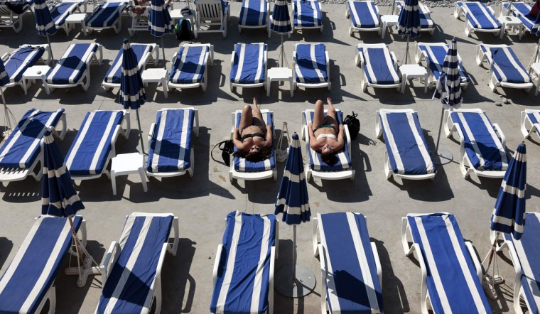 Two Finnish tourists enjoy a sunny and warm summer day on a private beach in Nice, August 21, 2014. (Eric Gaillard/Reuters)