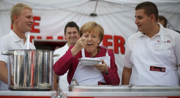 German Chancellor Angela Merkel tastes soup during her visit to a mobile kitchen of humanitarian aid organization 'Malteser' at the Federal Office of Civil Protection and Disaster Assistance (BBK) in Bonn August 19, 2014. (REUTERS/Ina Fassbender)